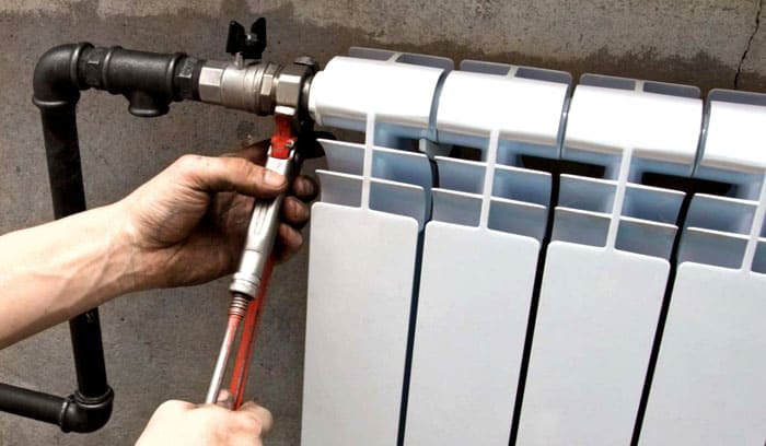 Закрепление радиатора при помощи трубного ключа