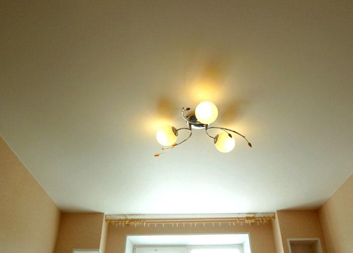Потолок лучше выбрать натяжной, глянцевый или тканевый, в зависимости от стиля