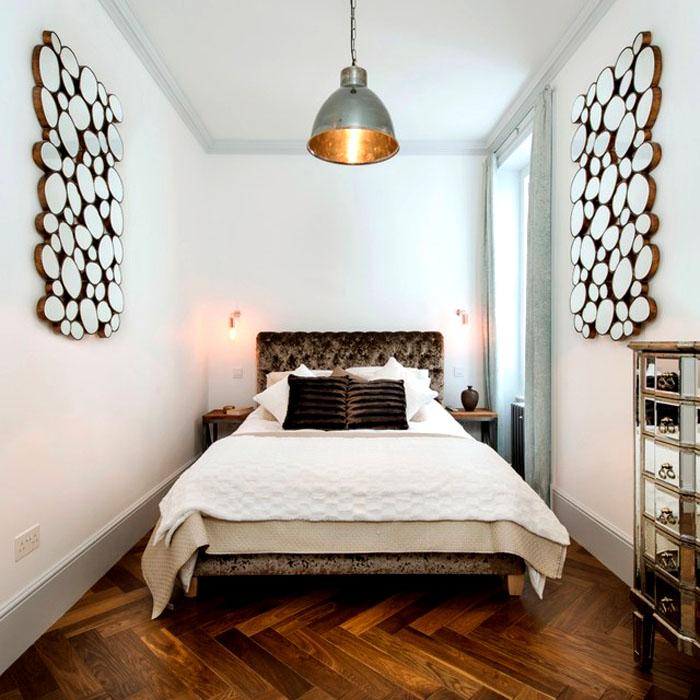 Узкое пространство можно визуально расширить, повесив на противоположных стенах яркие аксессуары, а кровать разметить по центру