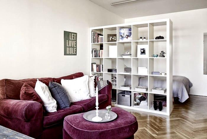В гостиной, которую нужно совместить со спальней, перегородками отделяют кровать от общей зоны