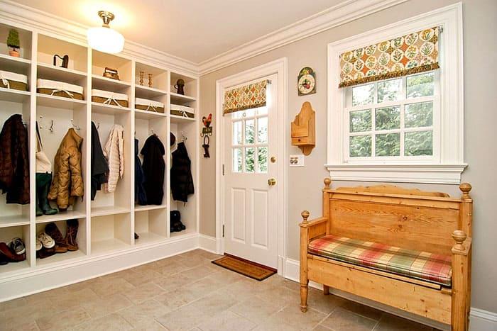 Одна из стен отдаётся под систему хранения, а неподалёку размещают скамеечку. Получается просто и уютно