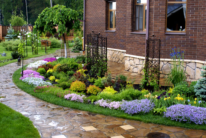 Придомовая территория оформляется по-разному: цветы, кустарники, деревья, созвучные наружному стилю постройки