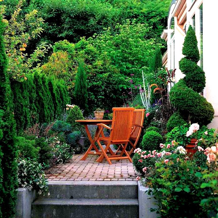 За домом можно сделать уютный уголок для отдых, красиво оформив его зеленью и садовой мебелью