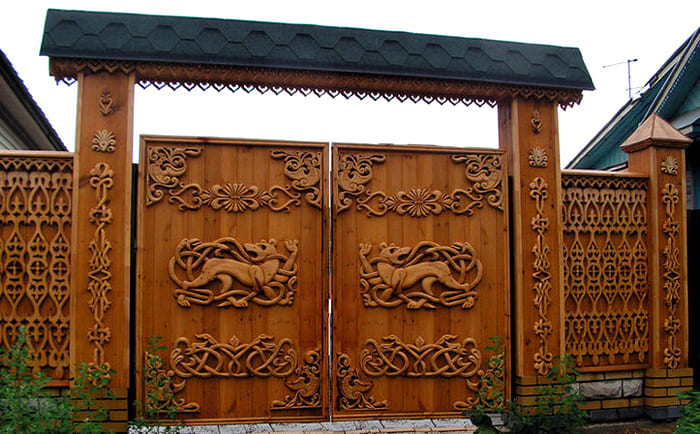 Резная калитка в заборе должна сочетаться по стилю с воротами