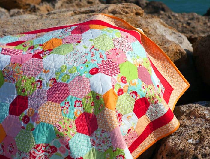 Лоскутное одеяло из треугольников дополнительно состоит из шестиугольных модулей