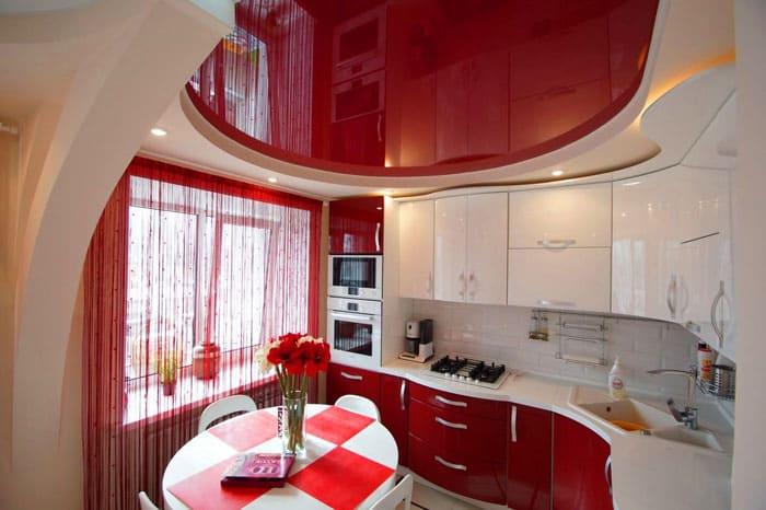 Красно-белый интерьер кухни смотрится интересно за счёт конструкции самого гарнитура и повторения его геометрической формы на потолке