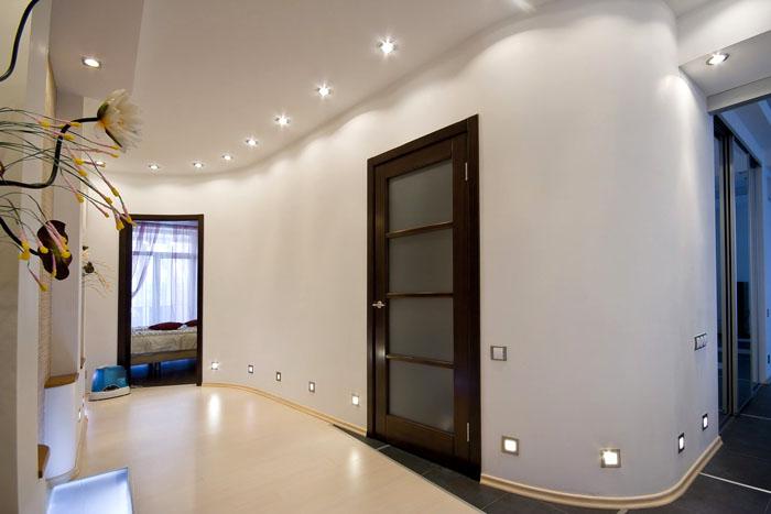 Длинные нестандартные коридоры можно декорировать подсветкой на разных уровнях
