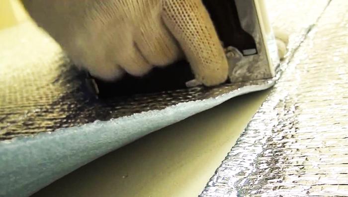 Процесс монтажа фольгированной подложки - её пристреливают строительным степлером к деревянному основанию