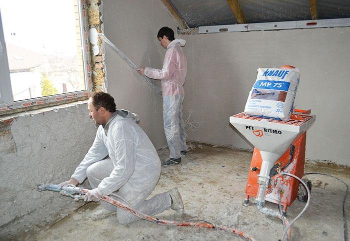 Процесс отделки стены при помощи штукатурной станции