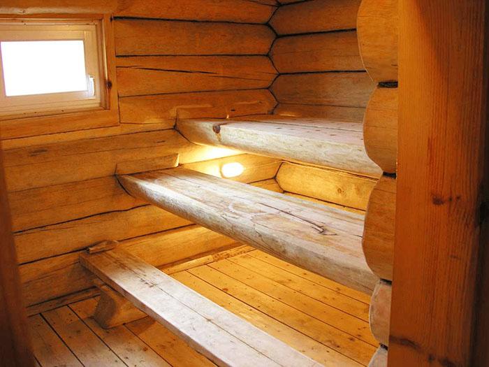 Массивные конструкции из необработанного бревна смотрятся идеально в банях из бруса