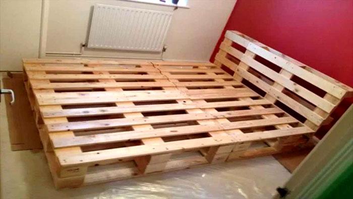 Каркас двуспальной кровати из поддонов может занимать практически всю площадь спальни, ведь от этой комнаты, кроме отдыха, больше ничего не требуется